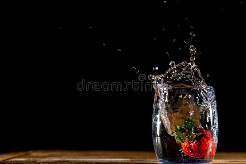 Foto av en röd jordgubbe som faller in i ett exponeringsglas av vatten och gör en färgstänk royaltyfri fotografi
