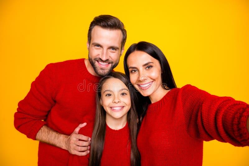 Foto av en rolig, söt, trevlig familj med dagens mamma som tar selfie och pappa kramar sin dotter med röd tröja royaltyfria bilder