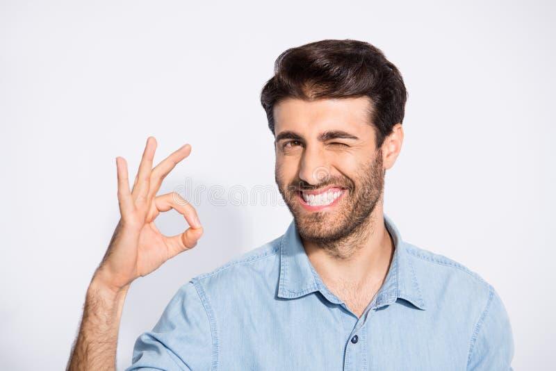 Foto av en snygg och mångetnisk kille som visar en okey-symbol som godkänner en god kvalitet på produktens vinkning av ögonkläder arkivfoto