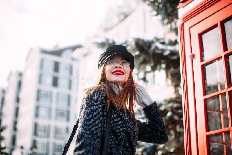 Foto av en ung härlig kvinna i trendigt lock på stadsgatan Slut upp ståenden av den charmiga damen lycklig flicka arkivfoton