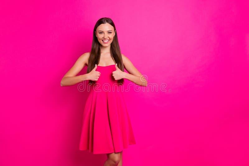 Foto av en vacker dam som höjer tummen och godkänner en god kvalitet på produkter som bär en snygg, snygg klänning på benaxarna royaltyfria foton