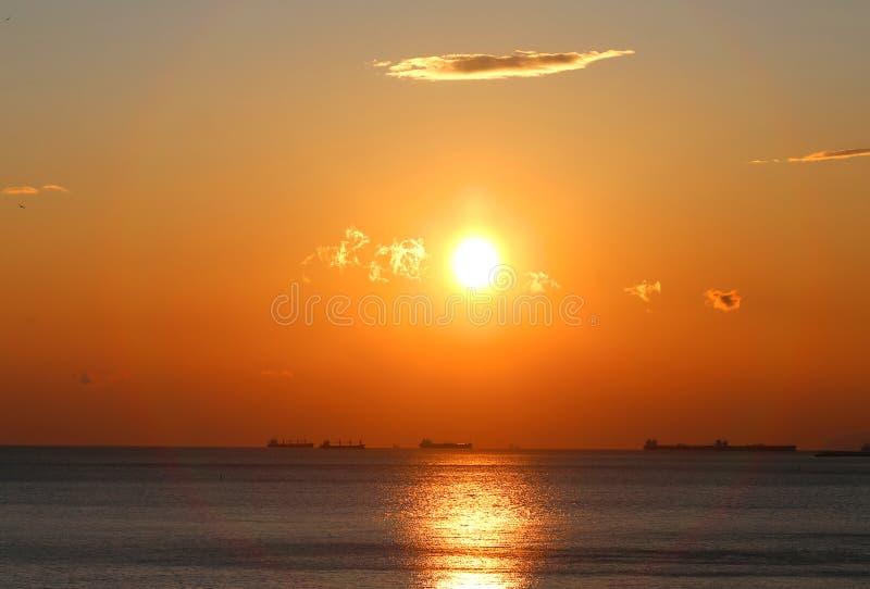Foto av en vacker solnedgång med moln längs havskusten royaltyfri fotografi