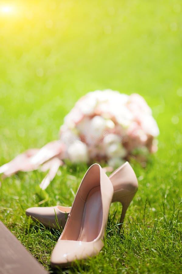 Foto av ett gifta sig par i sommaren Bruds skor på grönt textural gräs på bakgrunden av gifta sig en bukettnärbild arkivfoto