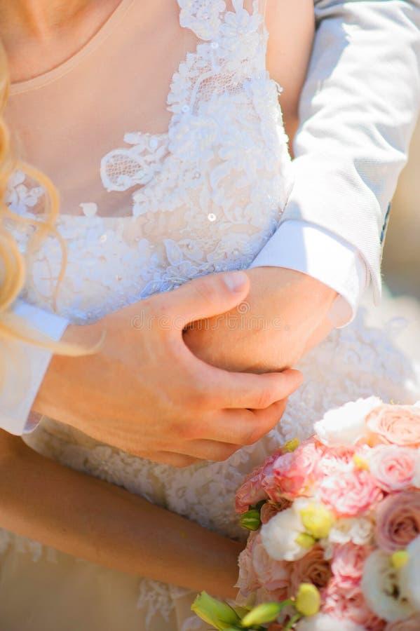 Foto av ett gifta sig par i sommaren Krama för brud och för brudgum, händer, cirklar och att gifta sig bukettnärbild- och kopieri arkivfoton