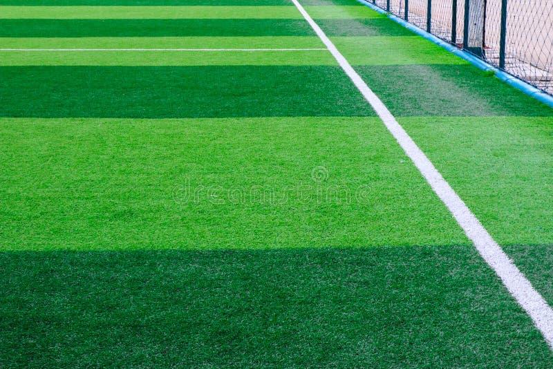 Foto av ett grönt syntetiskt grässportfält med den sh vita linjen arkivbild