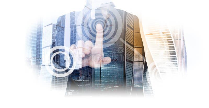 Foto av ett pekfinger av en lyckad affärsman i en dräkt och kontorsbyggnader, skyskrapor av en stad en dubbel utläggning Till royaltyfria foton