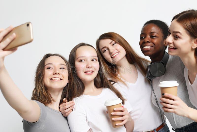 Foto av fem multietniska flickor som skrattar och tar selfie royaltyfria bilder