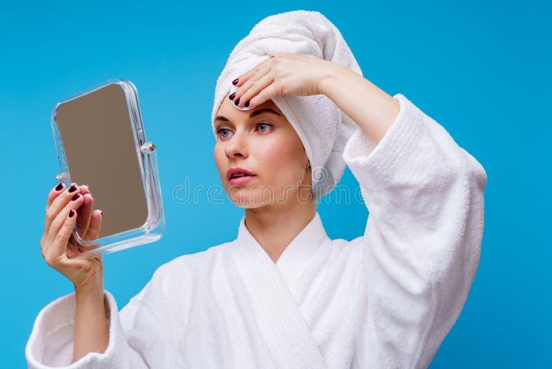 Foto av flickan i det vita laget och handduken p? hennes huvud med den bomullsblocket och spegeln i hennes hand royaltyfria bilder