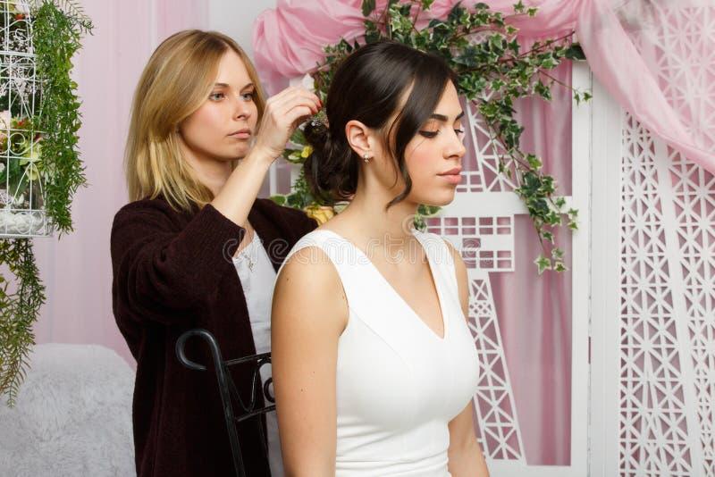 Foto av flickan och stylisten som justerar hår i rosa studio arkivfoto