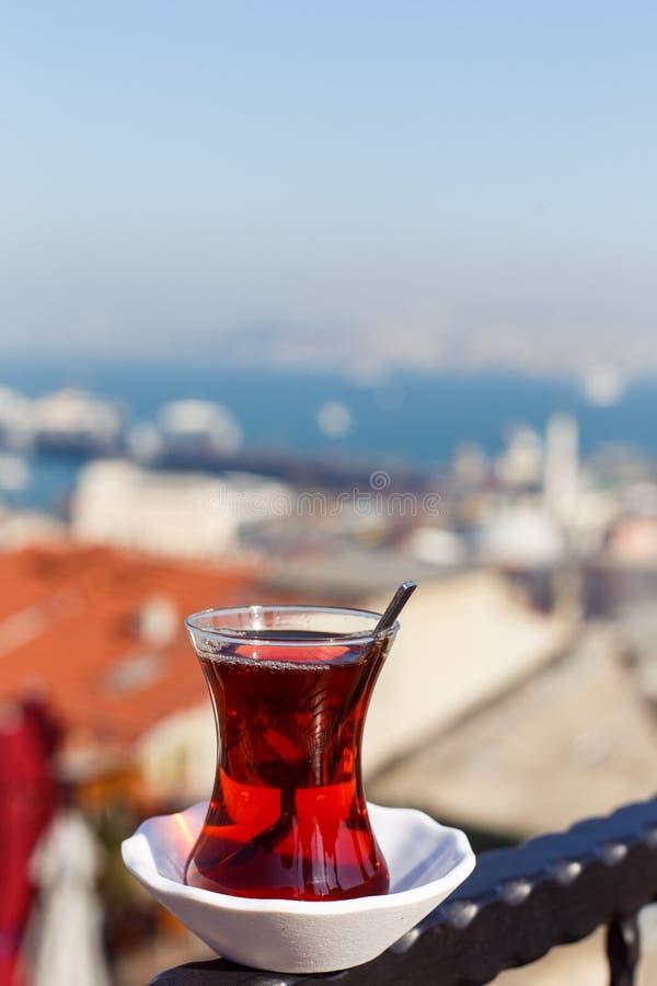 Foto av genomskinligt exponeringsglas med te på suddig bakgrund royaltyfri foto