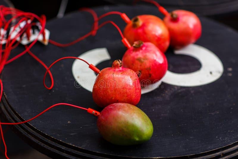 Foto av granatäpplen och mango med röda trådar på den svarta tabellen arkivbild