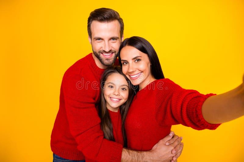 Foto av gudfruktiga, söta, älskvärda människor tillsammans med en pojkvän som kramar dotter med röda svettare royaltyfri foto