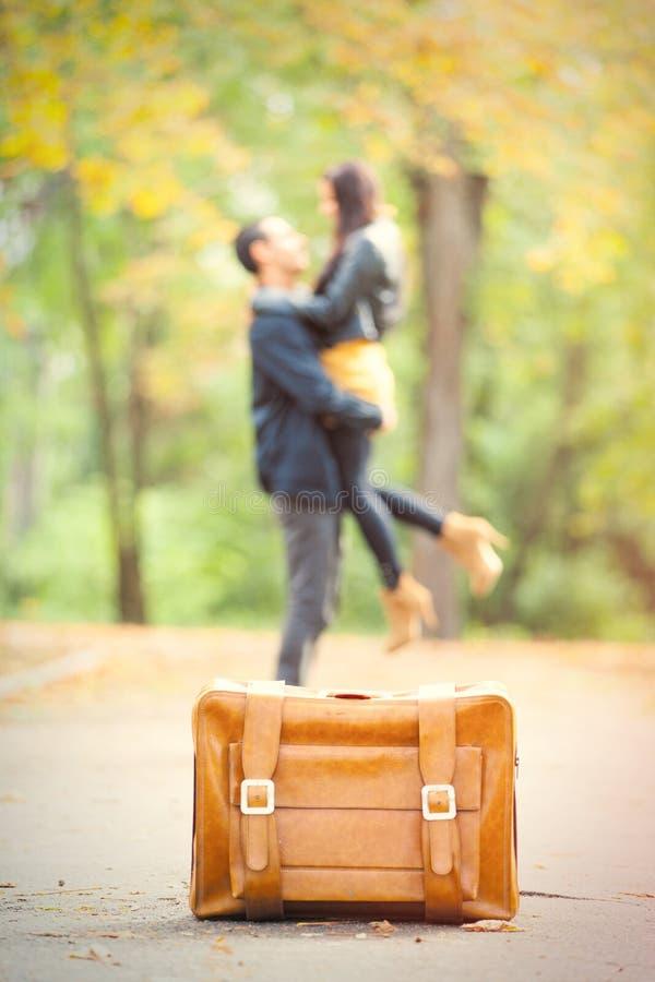 Foto av gulliga par som kramar nära resväskan på den underbara autuen arkivfoton