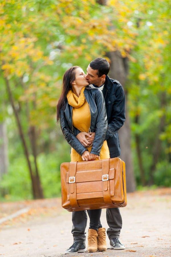Foto av gulliga par som kramar och kysser med resväskan på woen arkivbilder