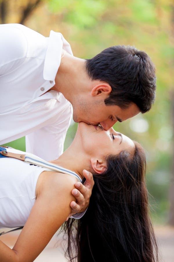 Foto av gulliga par som kramar och kysser på den underbara hösten fotografering för bildbyråer