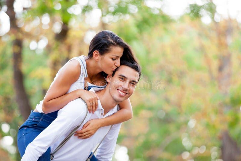 Foto av gulliga par som kramar och kysser på den underbara hösten royaltyfri bild