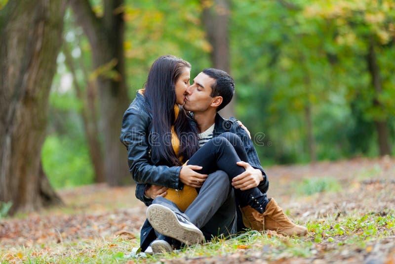 Foto av gulliga par som kramar och kysser på jordningen på woen royaltyfri bild