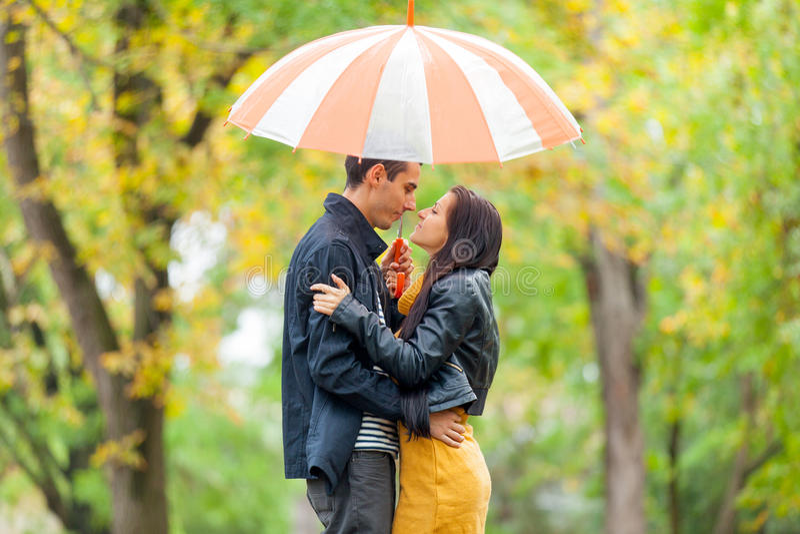 Foto av gulliga par som kramar under paraplyet på den underbara auten royaltyfri foto