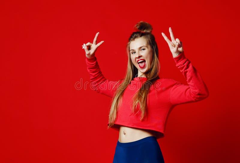Foto av härligt och att le, positiv flicka som visar fredsymbol och att se kameran som poserar på färgrik bakgrund arkivfoton