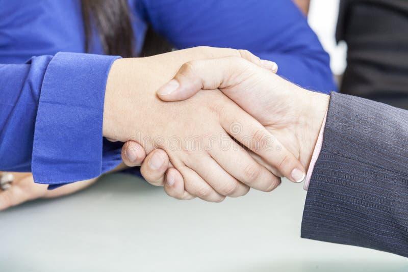 Foto av handskakningen av affärspartners, når underteckning av avtalet arkivfoton