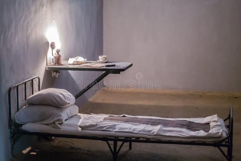 Foto av inre av fängelset säng och skrivbord med lampan arkivfoto