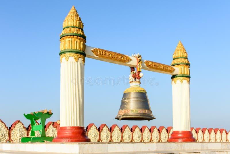 Foto av kopparklockan med två konkreta högar royaltyfri bild