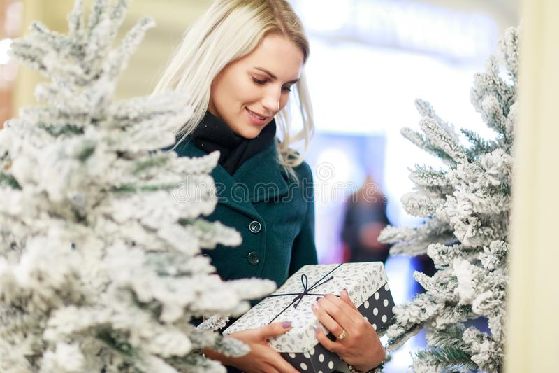 Foto av kvinnan med gåvan i ask av den vita julgranen arkivbild