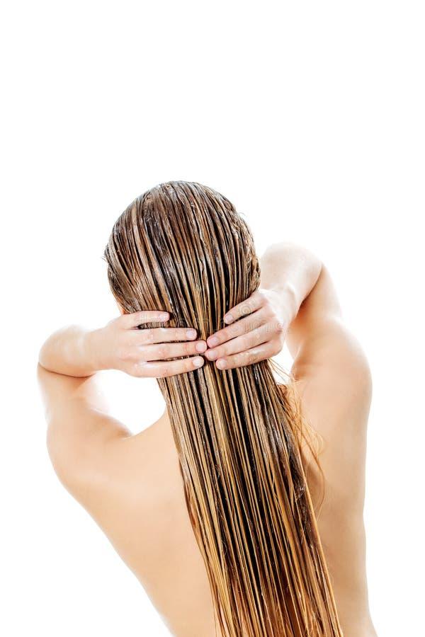 Foto av kvinnan som applicerar hårhårbalsamen fotografering för bildbyråer