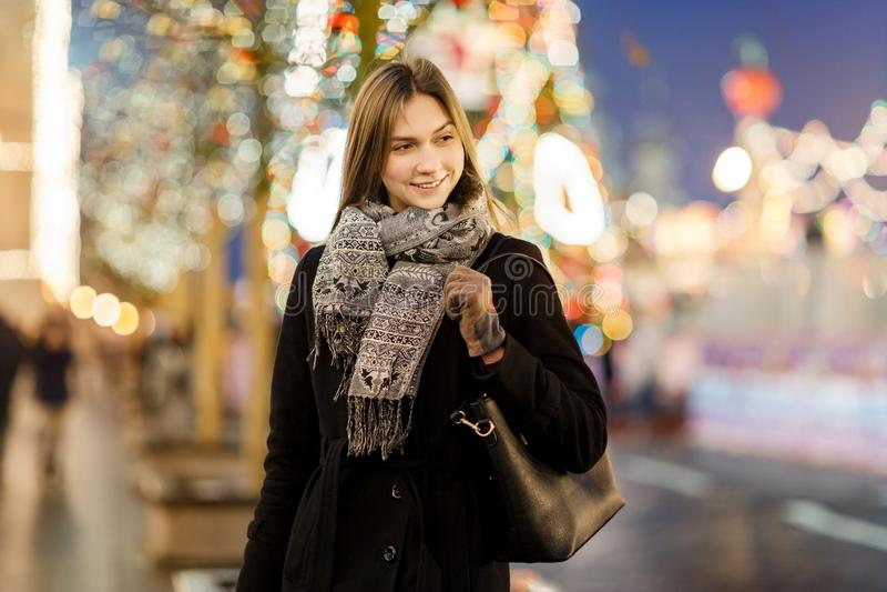 Foto av kvinnan utanför i stad på suddig bakgrund med girlanden royaltyfria foton