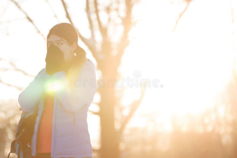 Foto av kvinnavärmehänder i vinter i trän på eftermiddagen fotografering för bildbyråer
