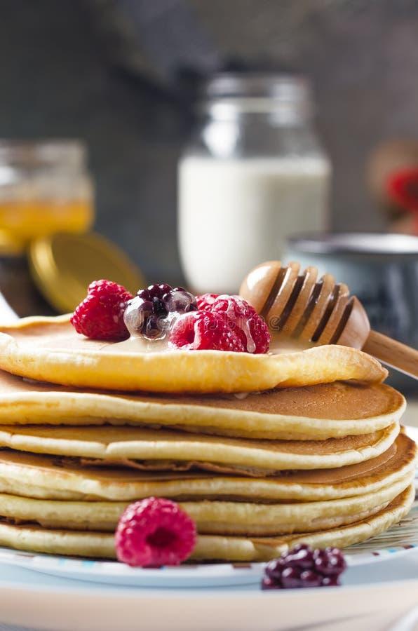 Foto av läckra pannkakor med bär och honung över trät royaltyfri fotografi