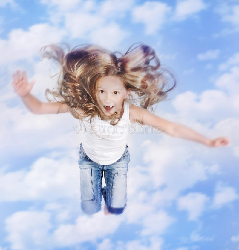 Foto av liten flicka som hoppar över blåttskyen med moln royaltyfria bilder