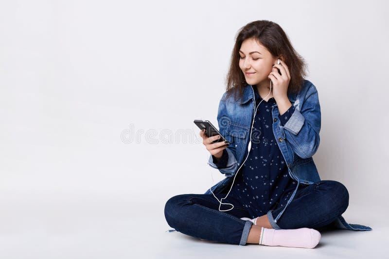 Foto av lycklig le härlig flickamessaging via samkvämnätverk och användahörlurar för att lyssna till musik som ser kopplad av och royaltyfri foto