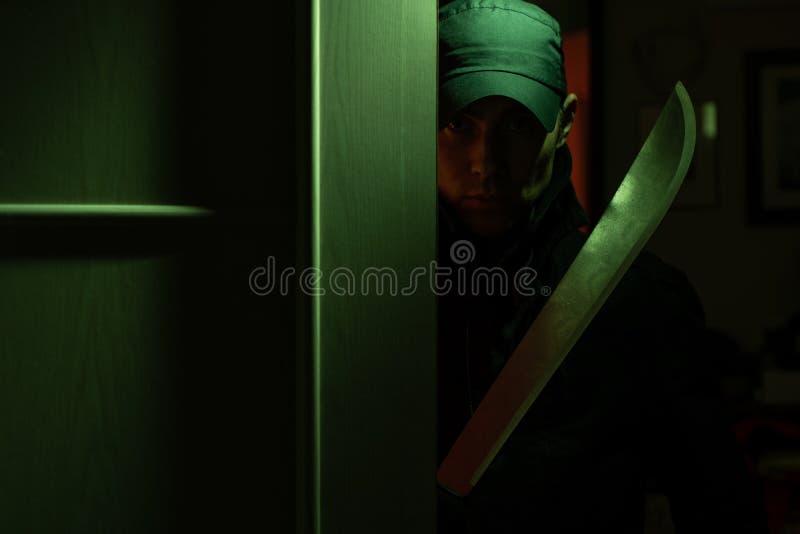 Foto av mördaremannen med machetet i mörk lägenhet med klartecken royaltyfria foton