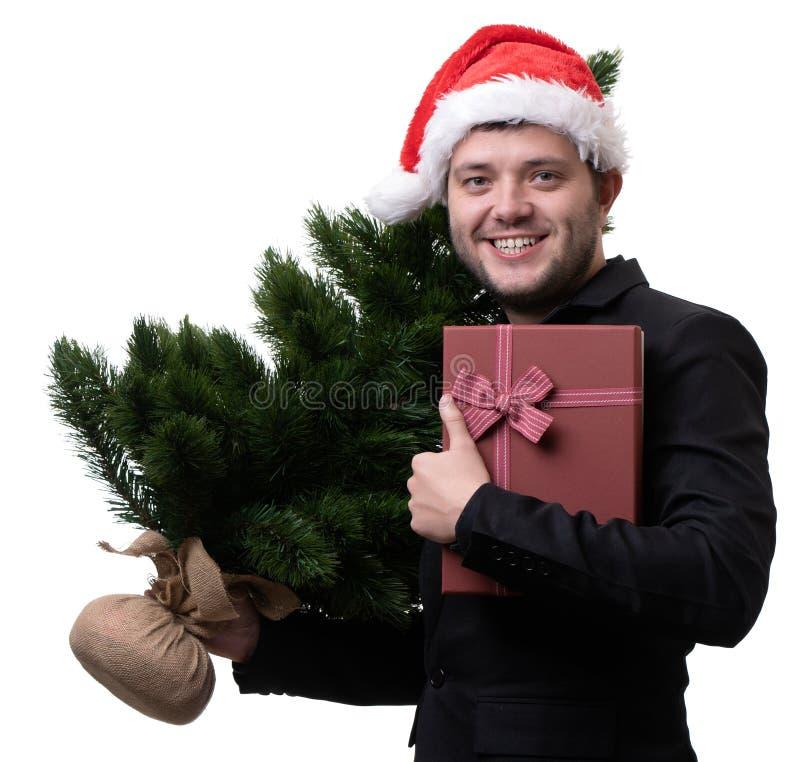 Foto av mannen i jultomtenhatt med julgranen med asken med gåvan fotografering för bildbyråer
