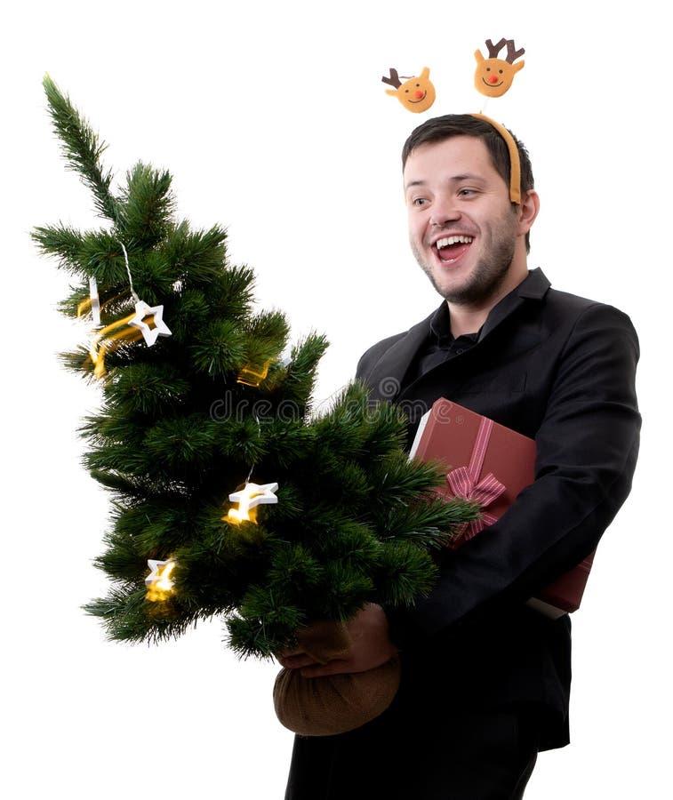 Foto av mannen i kant med hjortar med julgranen och gåvan i händer royaltyfri foto
