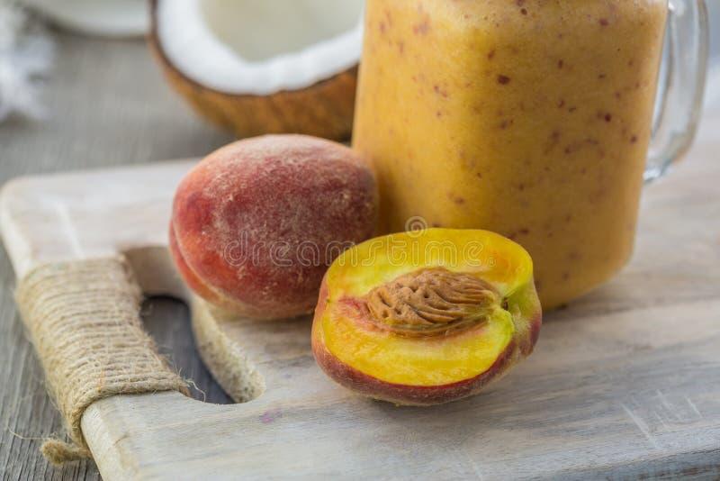 Foto av persikasmoothien i krus med sugrör på ljus bakgrund Ny organisk smoothie H?lsa eller detoxen bantar matbegrepp arkivfoto