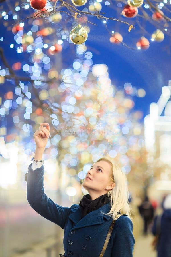 Foto av rörande julleksaker för härlig flicka på träd royaltyfria foton