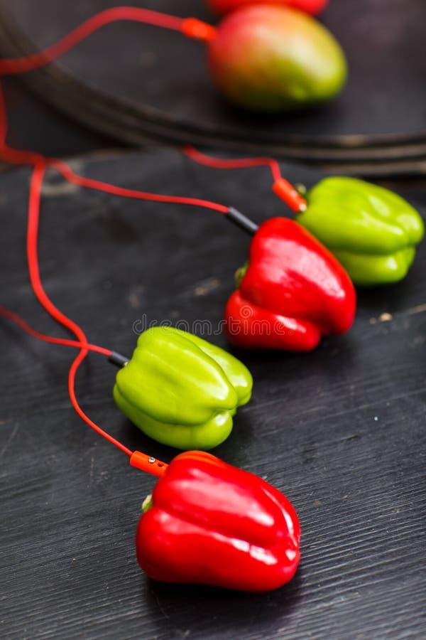 Foto av rött och paprika, avokado med röda trådar på den svarta tabellen royaltyfri foto