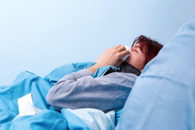 Foto av sidan av den sjuka brunetten som blåser hennes näsa i pappersnäsduken som ligger i säng arkivfoton