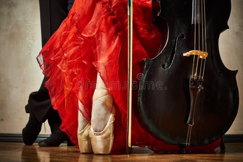 Foto av skor och violoncellen för balettpointe- och latindansare arkivbild