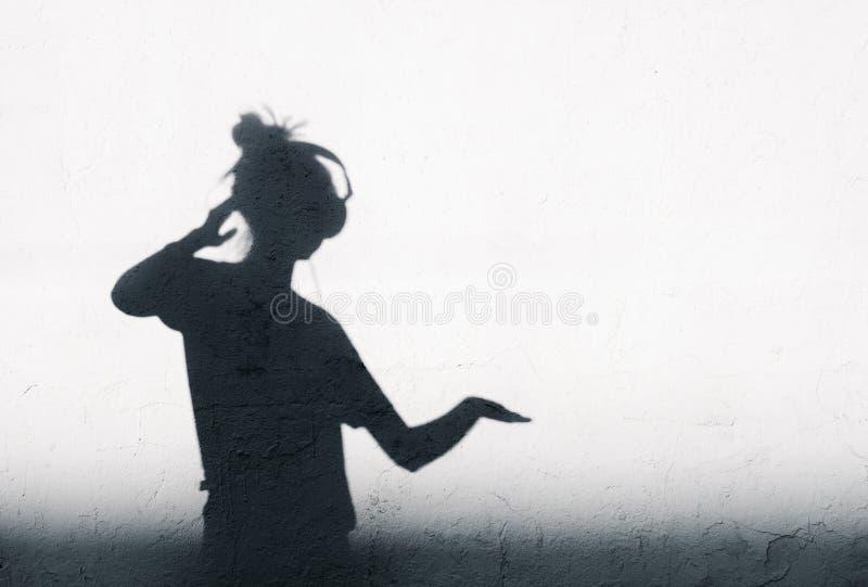 Foto av skuggor av dj-kvinnan med hörlurar royaltyfri bild