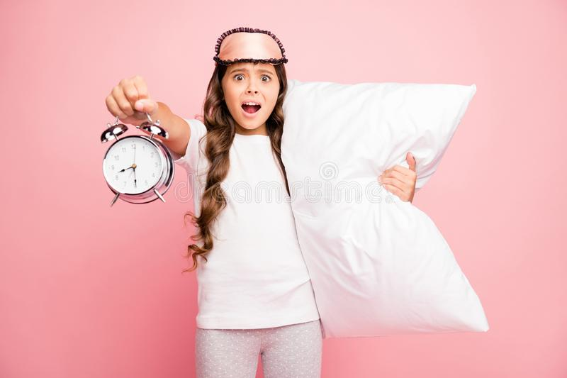 Foto av sorgliga, olyckliga flickor som kramar sin kudde med klockor som har försovit sig och som är sena på isolerad pastel i sk royaltyfri fotografi