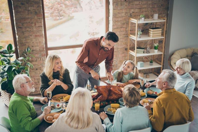 Foto av stora familjen: Sträck på matbordet runt semesterrostad kalkonpappa som tillverkar skivor hungriga släktingar arkivfoton