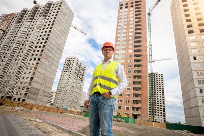 Foto av teknikern i hardhat mot konstruktionsplats royaltyfri bild
