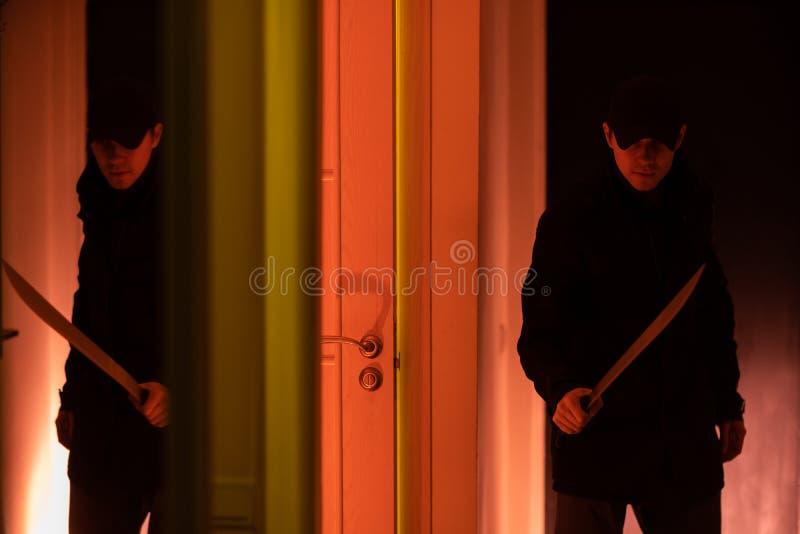 Foto av tjuven med machetet i mörkt rum med rött ljus royaltyfri fotografi