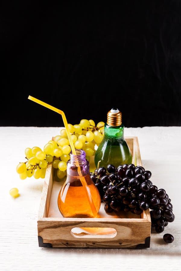 Foto av trämagasinet med gräsplan- och svartdruvor, två flaskor av fruktsaft arkivbild