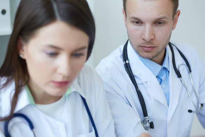 Foto av två doktorer som diskuterar tillsammans den nya vägen av behandling, medan ha ett möte på kontoret royaltyfria foton