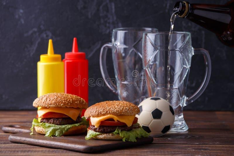 Foto av två hamburgare, exponeringsglas, fotbollboll, ketchup fotografering för bildbyråer