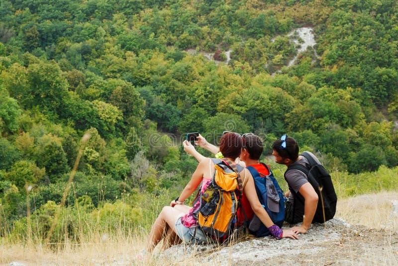 Foto av två män och kvinnan som tar selfie, medan sitta på backen med vegetation royaltyfri fotografi